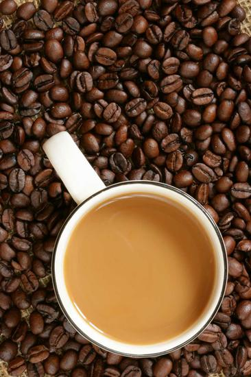 Cup of coffee with milk over coffee beans background, view from above