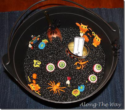 black cauldron filled with Halloween objects