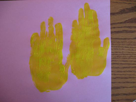Two yellow hand prints on pink construction paper